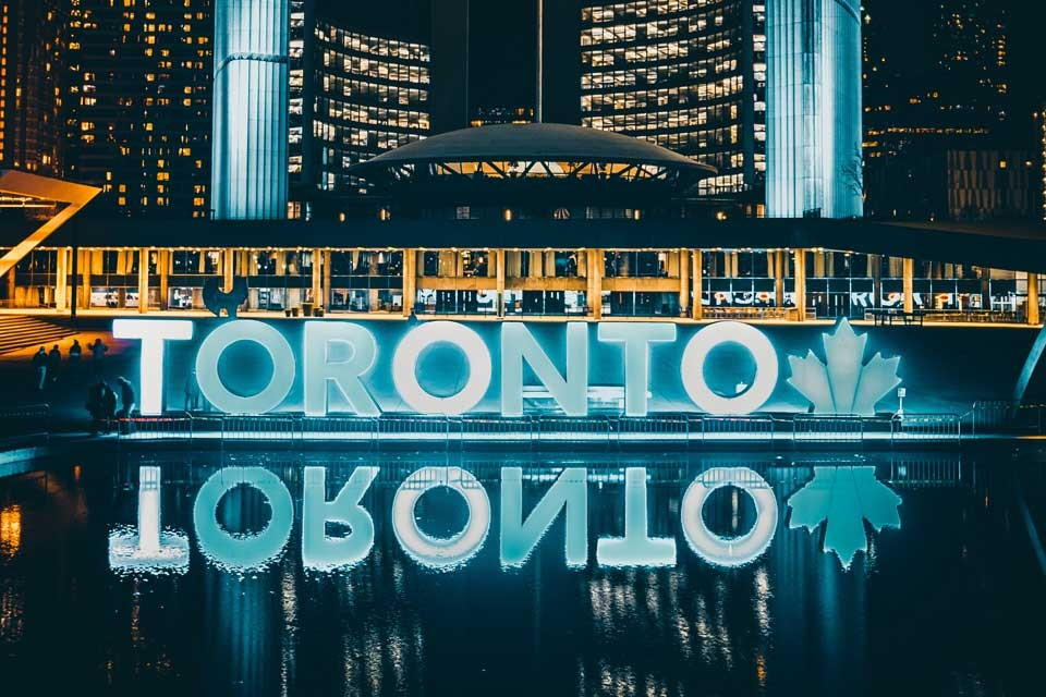Image of a sign of Toronto lit up at night
