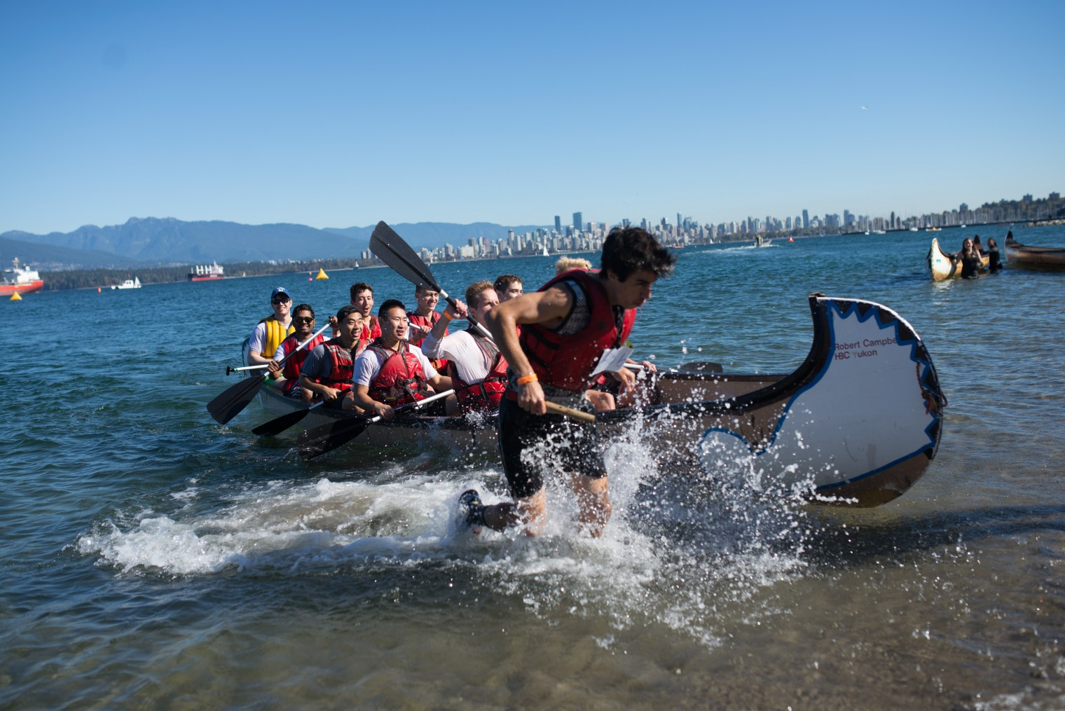 A team of 10 students paddle to shore at Day of the Longboat competition