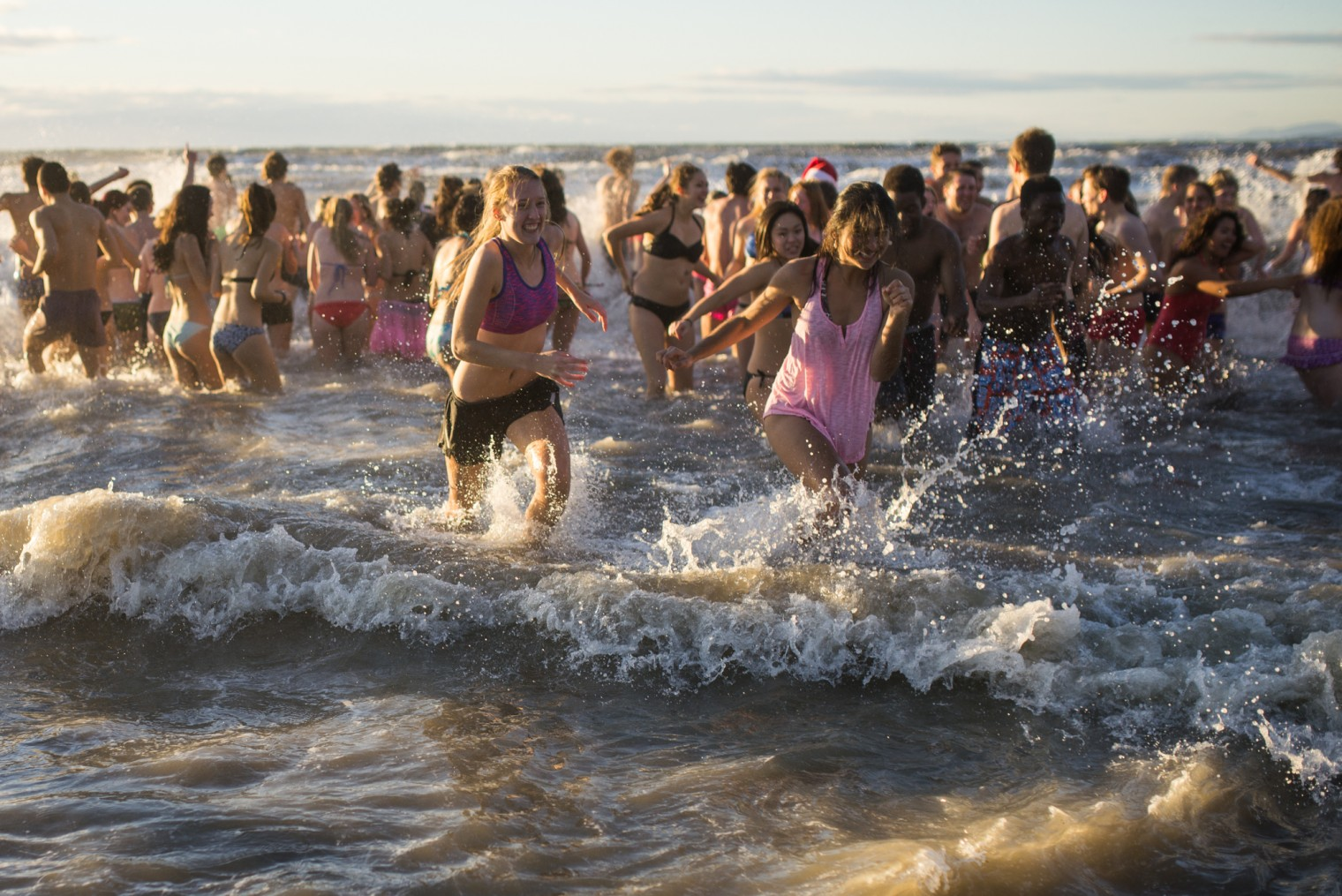 Students run out of the cold ocean water during the Polar Bear Swim at Wreck Beach