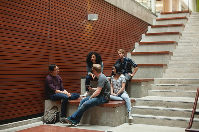 Students sitting on steps inside UBC Sauder Building