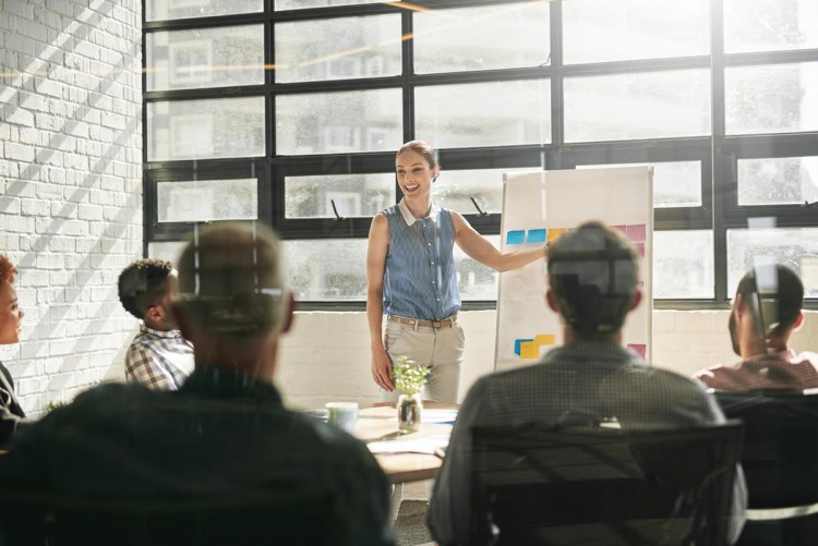 Image of woman presenting in a meeting room full of people