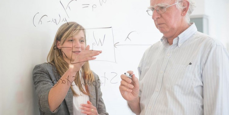 Image of professor and student writing on glass