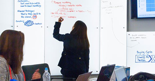 Student or instructor writing on a whiteboard in front of the class