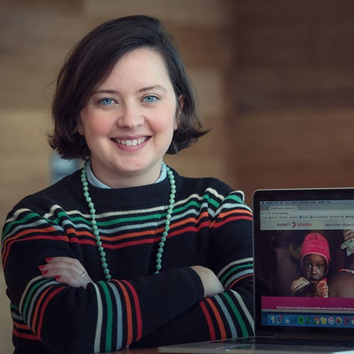 Image of Alumni student Kate Hyde sitting and leaning on a wooden table with a laptop in front of her