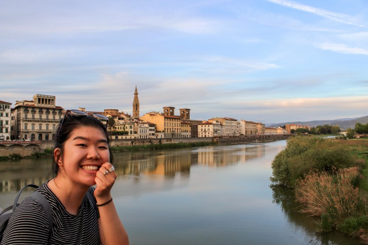 Student smiles in front of the Arno River in Florence, Italy