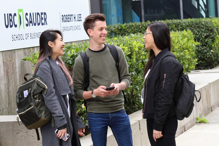 Three students wearing backpacks laugh together in front of the UBC Sauder School of Business sign