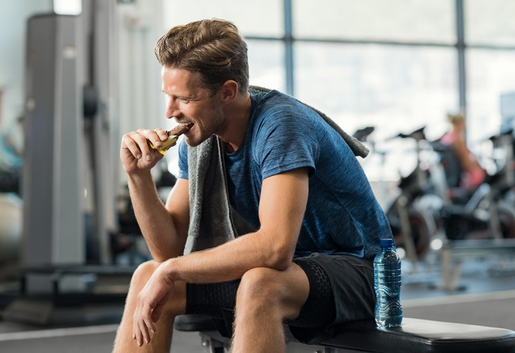 Male eating an energy bar inside a gym.