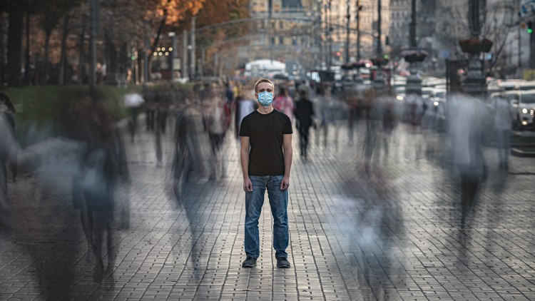 A man wearing a mask on the street.