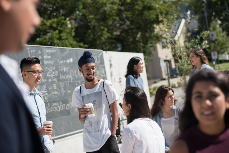 Students meet together for coffee in an outdoor courtyard