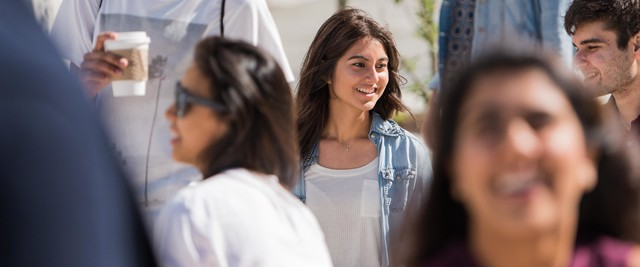 Image of female student among other students walking