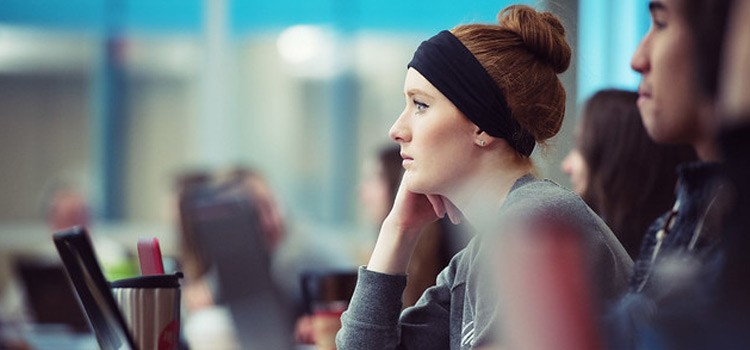 Image of female student sitting in class with other students listening